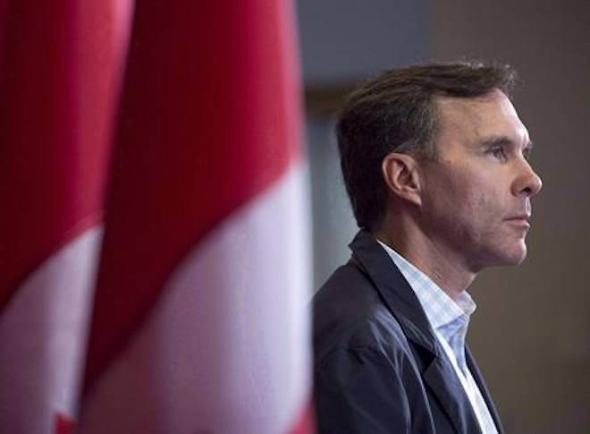 Finance Minister Bill Morneau takes questions as the Liberal cabinet meets in St. John's, N.L. on Tuesday, Sept. 12, 2017. The federal ethics commissioner has cleared Finance Minister Bill Morneau of insinuations that both he and his father benefited from insider information to save half a million dollars on the sale of shares in the family-built company. THE CANADIAN PRESS/Andrew Vaughan