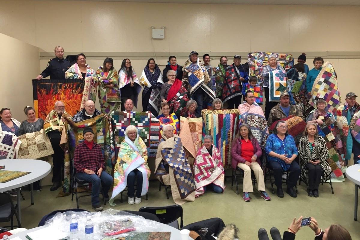 Residents of the Ashcroft Reserve and Boston Flats Trailer Park gathered in Ashcroft on November 5 to receive handmade quilts. The project was the brainchild of Spences Bridge resident Judy Draney (seated far left, front row). Photo: Kris Hardy.