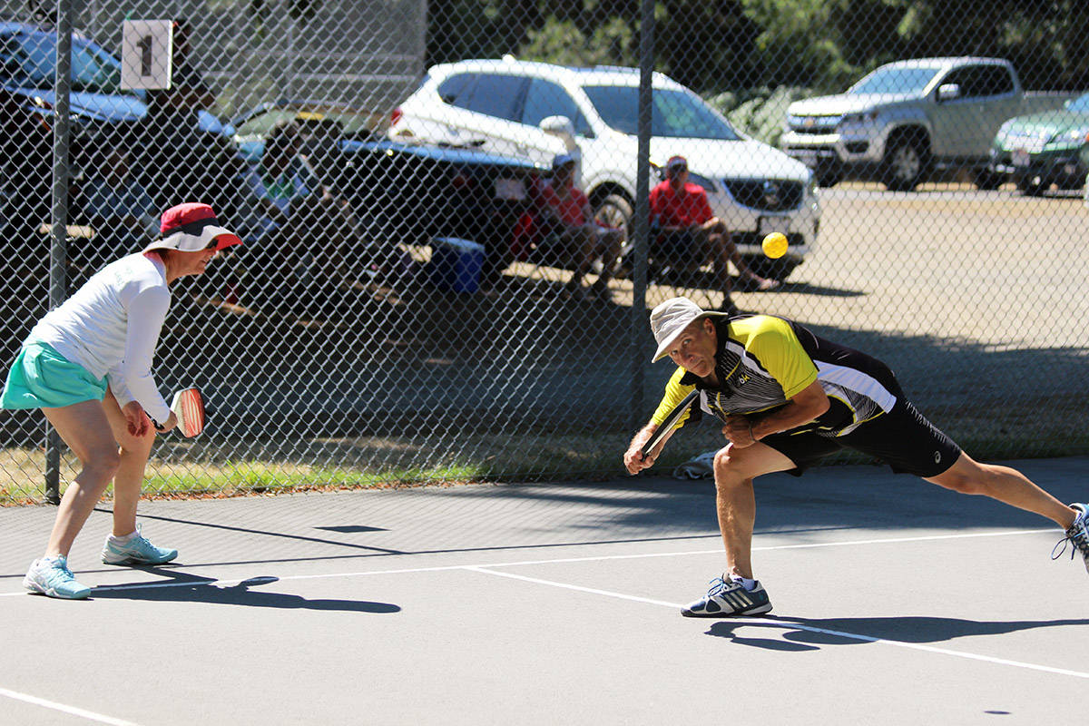 Peter Brix of Victoria goes low to send this shot back over the net. (Photo by Don Bodger)