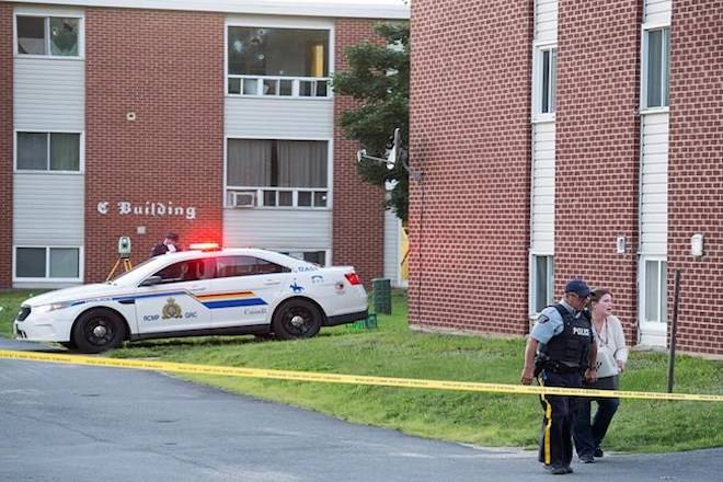 An RCMP officer and a resident carry a pet container from an evacuated apartment building in Fredericton on Friday, August 10, 2018. Two city police officers were among four people who died in a shooting in the residential area on the city's north side. THE CANADIAN PRESS/Andrew Vaughan