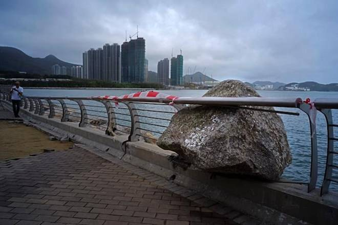 A big rock, which was blowed by Typhoon Mangkhut is stuck in between the fence on the waterfront of a house estate in Hong Kong, Monday, Sept. 17, 2018. (AP Photo/Vincent Yu)