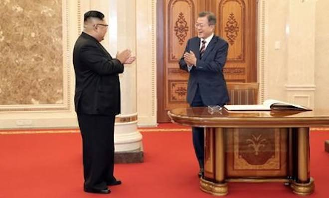 South Korean President Moon Jae-in, right, and North Korean leader Kim Jong Un react after signing a guest book before their summit at the headquarters of the Central Committee of the Workers' Party in Pyongyang, North Korea, Tuesday, Sept. 18, 2018. (Pyongyang Press Corps Pool via AP)