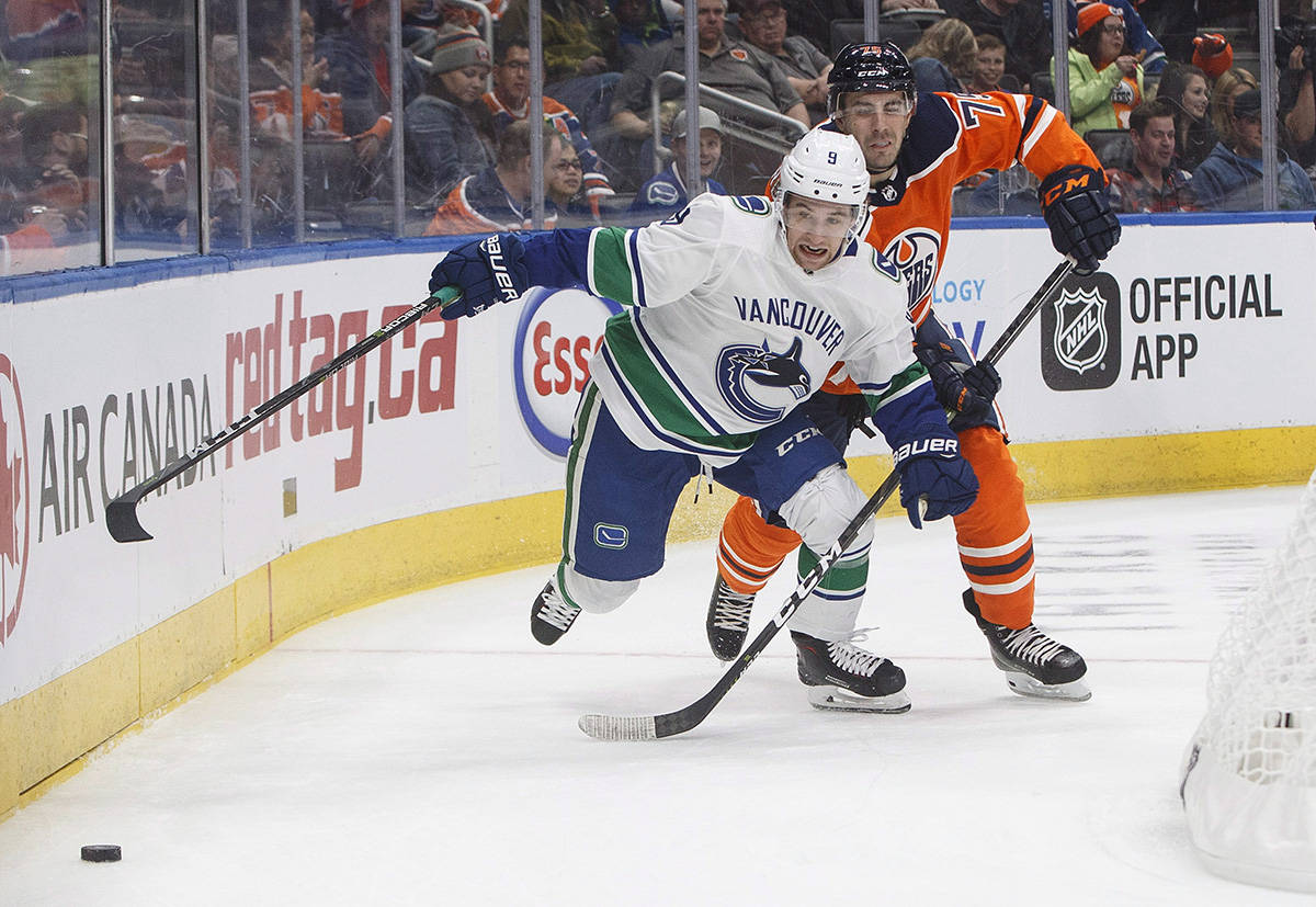 Vancouver Canucks' Brendan Leipsic (9) and Edmonton Oilers' Evan Bouchard (75) battle for the puck during first period pre-season action in Edmonton, Alta., on Tuesday September 25, 2018. THE CANADIAN PRESS/Jason Franson