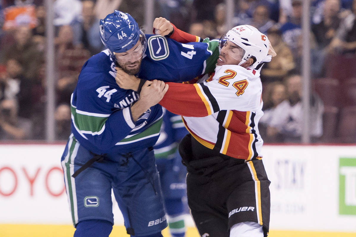 Vancouver Canucks defenceman Erik Gudbranson (44) fights with Calgary Flames defenceman Travis Hamonic (24) during first period NHL action at Rogers Arena in Vancouver, Wednesday, Oct, 3, 2018. THE CANADIAN PRESS/Jonathan Hayward