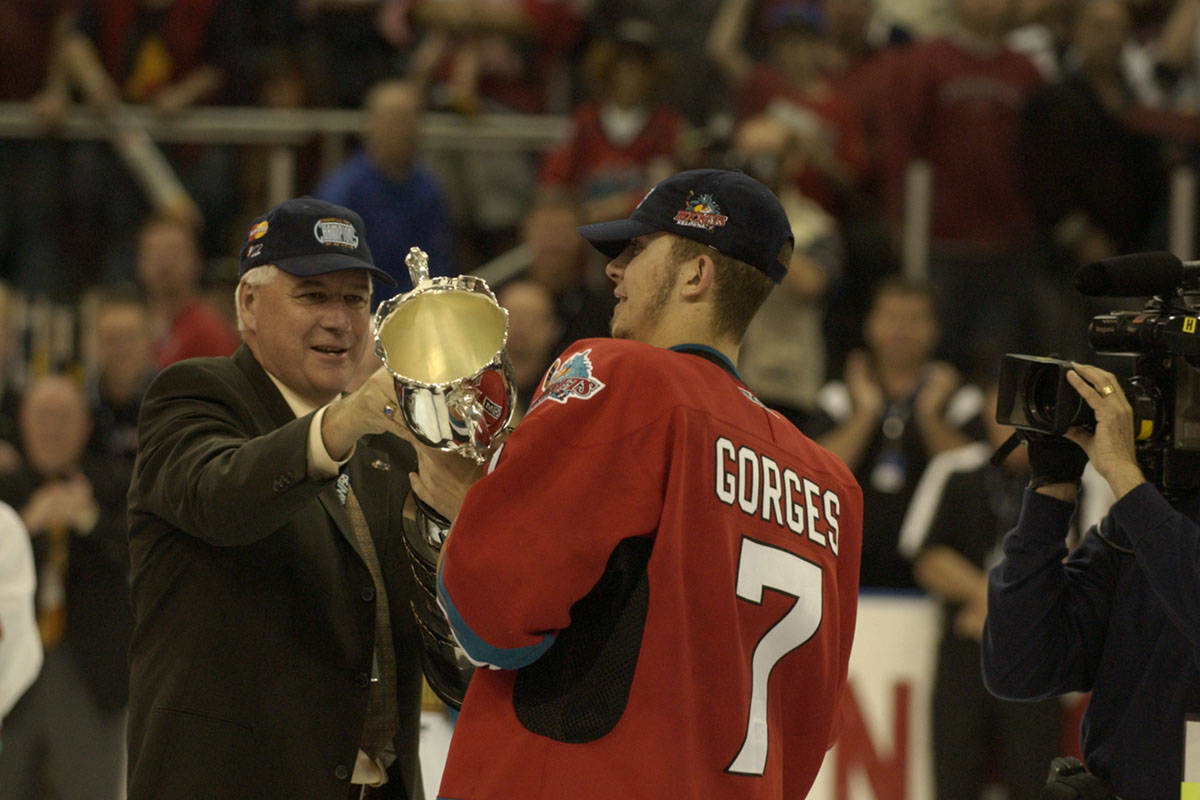 Capital News file                                Bruce Hamilton hands the Memorial Cup to team captain Josh Gorges in the celebration at Prospera Place after the host Kelowna Rockets won the Canadian Hockey League championship in 2004.