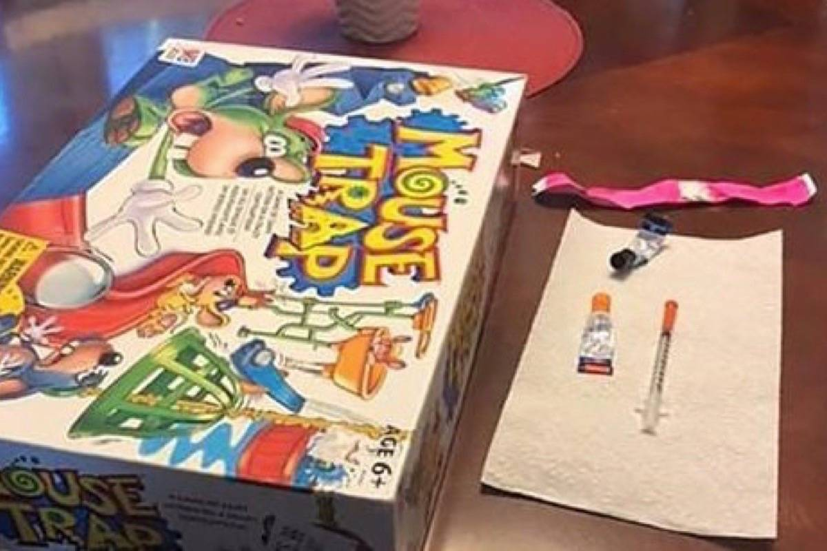A board game, syringe and glue. (Mitch Selman via THE CANADIAN PRESS)