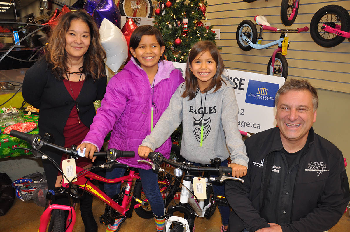 Tracey Morrison, owner of DLC Lighthouse Mortgage, left, and Will Arnold of Experience Cycling with two of the 10 youngsters who will be receiving new bikes just in time for Christmas. (Warren Goulding/Citizen)