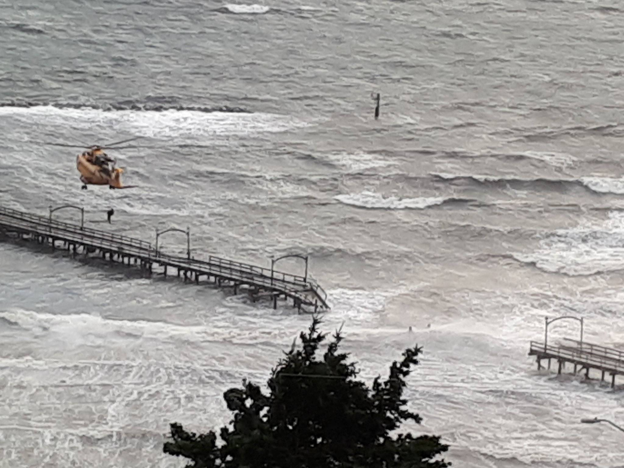 Search and Rescue working to grab the person trapped on the end of the pier. (Sheila LaRose/Twitter)