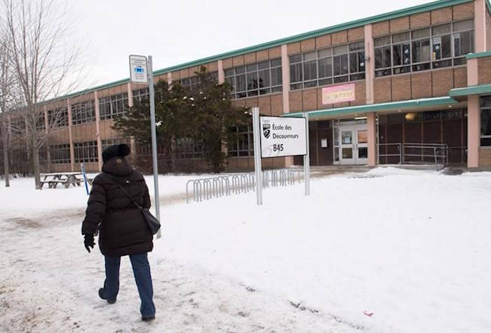 A woman walks by Ecole des Decouvreurs in the Montreal borough of Lasalle where children and staff were evacuated from the elementary school after a carbon monoxide leak on Monday, January 14, 2019; THE CANADIAN PRESS/Graham Hughes
