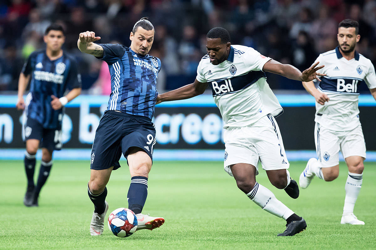 Los Angeles Galaxy's Zlatan Ibrahimovic (9) passes the ball as Vancouver Whitecaps' Doneil Henry (2) defends during the first half of an MLS soccer game in Vancouver, on Friday April 5, 2019. THE CANADIAN PRESS/Darryl Dyck