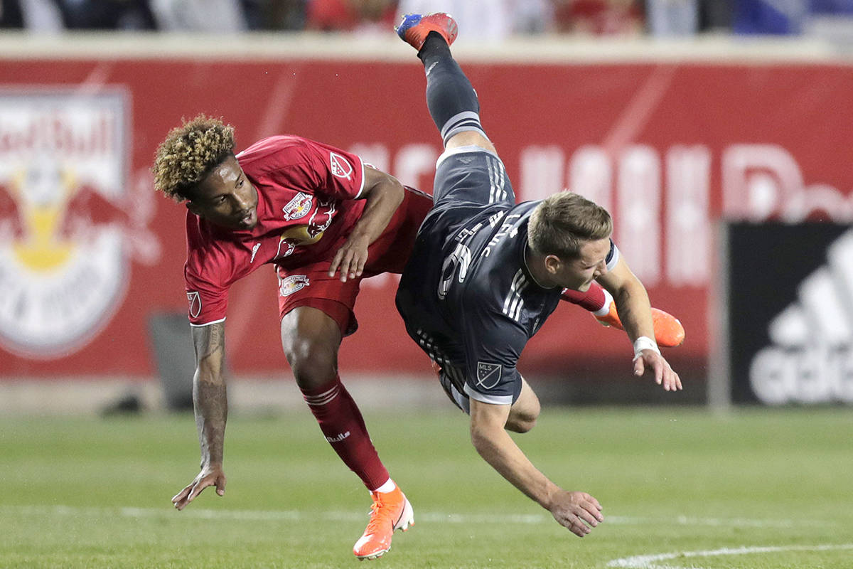 New York Red Bulls defender Kyle Duncan, left, and Vancouver Whitecaps midfielder Brett Levis collide while competing for the ball during the first half of an MLS soccer match Wednesday, May 22, 2019, in Harrison, N.J. (AP Photo/Julio Cortez)