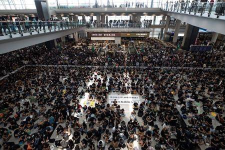 """Protesters surround banners that read: """"Those on the street today are all warriors!"""" centre top, and """"Release all the detainees!"""" during a sit-in rally at the arrival hall of the Hong Kong International airport in Hong Kong, Monday, Aug. 12, 2019. (AP Photo/Vincent Thian)"""