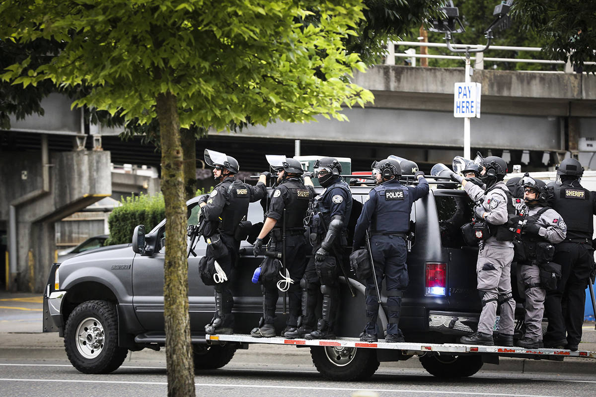 Portland Police prepare to head towards Tom McCall Waterfront Park as right-wing groups and counterprotesters gathered in downtown Portland, Ore., on Saturday, Aug. 17, 2019. Flag-waving members of the Proud Boys and Three Percenters militia group began gathering late in the morning, some wearing body armor and helmets. Meanwhile black clad, helmet and mask-wearing anti-fascist protesters — known as antifa — were also among the several hundred people on the streets. (AP Photo/Moriah Ratner)