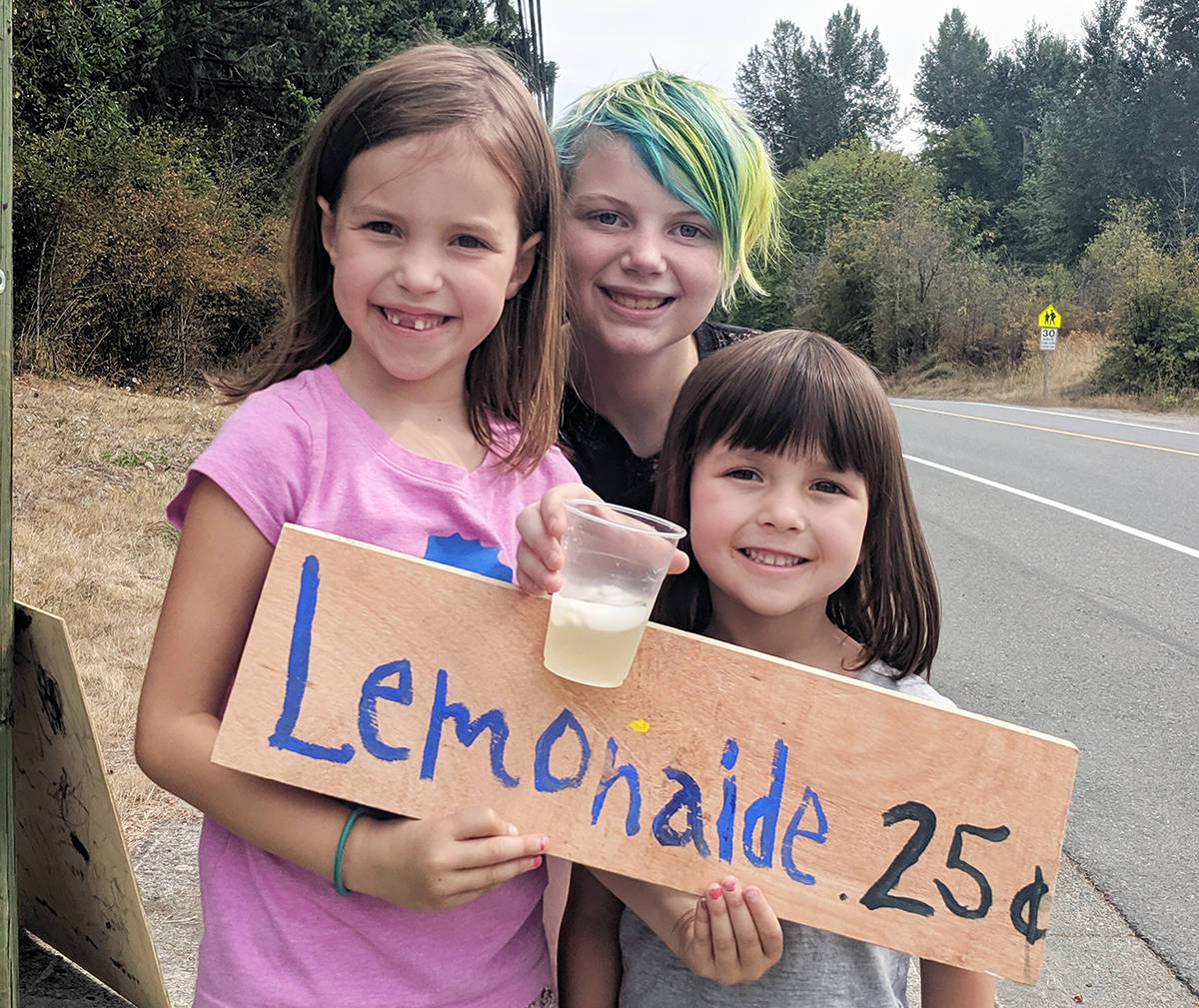 Come and get it! Abby Knight (back) and Violet and Adelaide Starr offer lemonade at a stand on Chemainus Road just like kids used to do in the olden days. (Photo by JoHannah Knight)