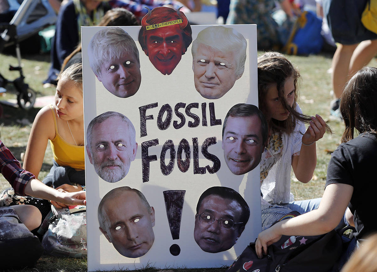 Climate protesters hold a banner bearing the images of world leaders as they demonstrate in London, Friday, Sept. 20, 2019. Protesters around the world joined rallies on Friday as a day of worldwide demonstrations calling for action against climate change began ahead of a U.N. summit in New York. (AP Photo/Frank Augstein)