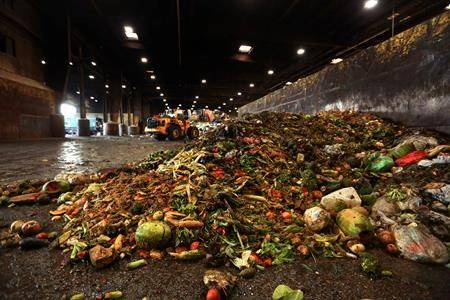 """In this Aug. 29, 2018, photo, at the Waste Management facility in North Brooklyn, tons of leftover food sits piled up before being processed into """"bio-slurry,"""" in New York. A team of scientists spent weeks combing through the garbage of dozens of households to come up with what they say is the most accurate measure yet of how much food is wasted in Canadian kitchens. (THE CANADIAN PRESS/AP/Stephen Groves)"""