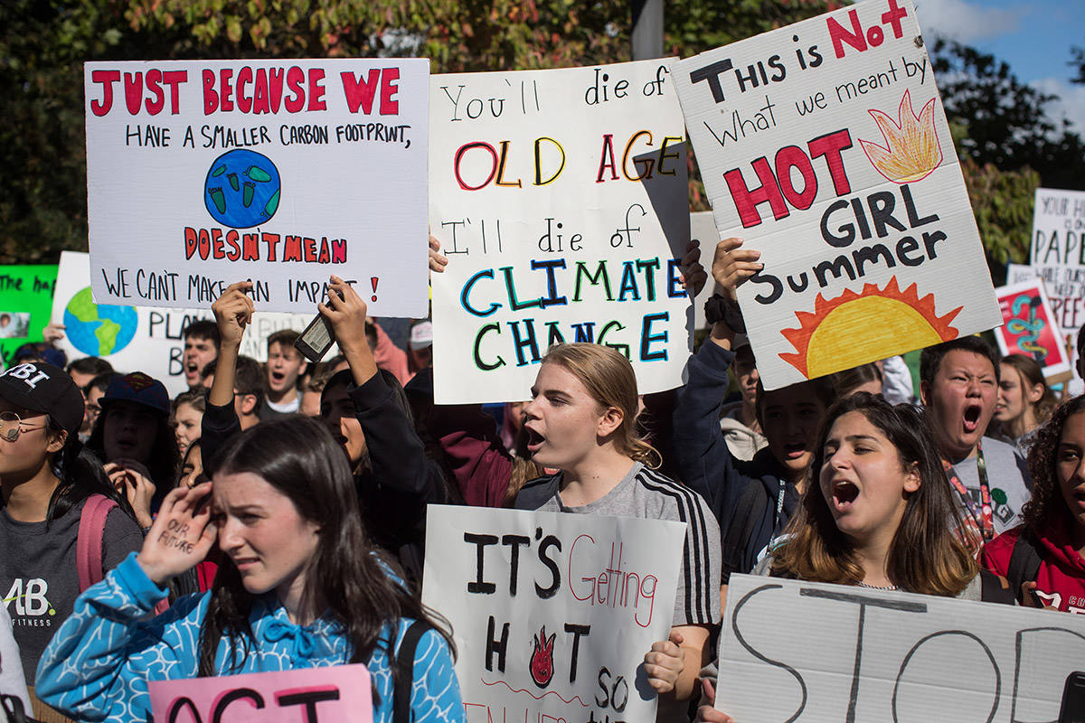 People hold signs as thousands gather outside Vancouver City Hall before marching downtown during a climate strike in Vancouver on Friday, Sept. 27, 2019. THE CANADIAN PRESS/Darryl Dyck
