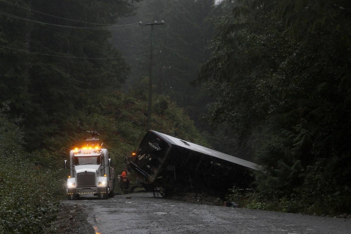 A tow-truck crew removes a bus from an embankment next to a logging road near Bamfield, B.C., Saturday, Sept. 14, 2019. THE CANADIAN PRESS/Chad Hipolito