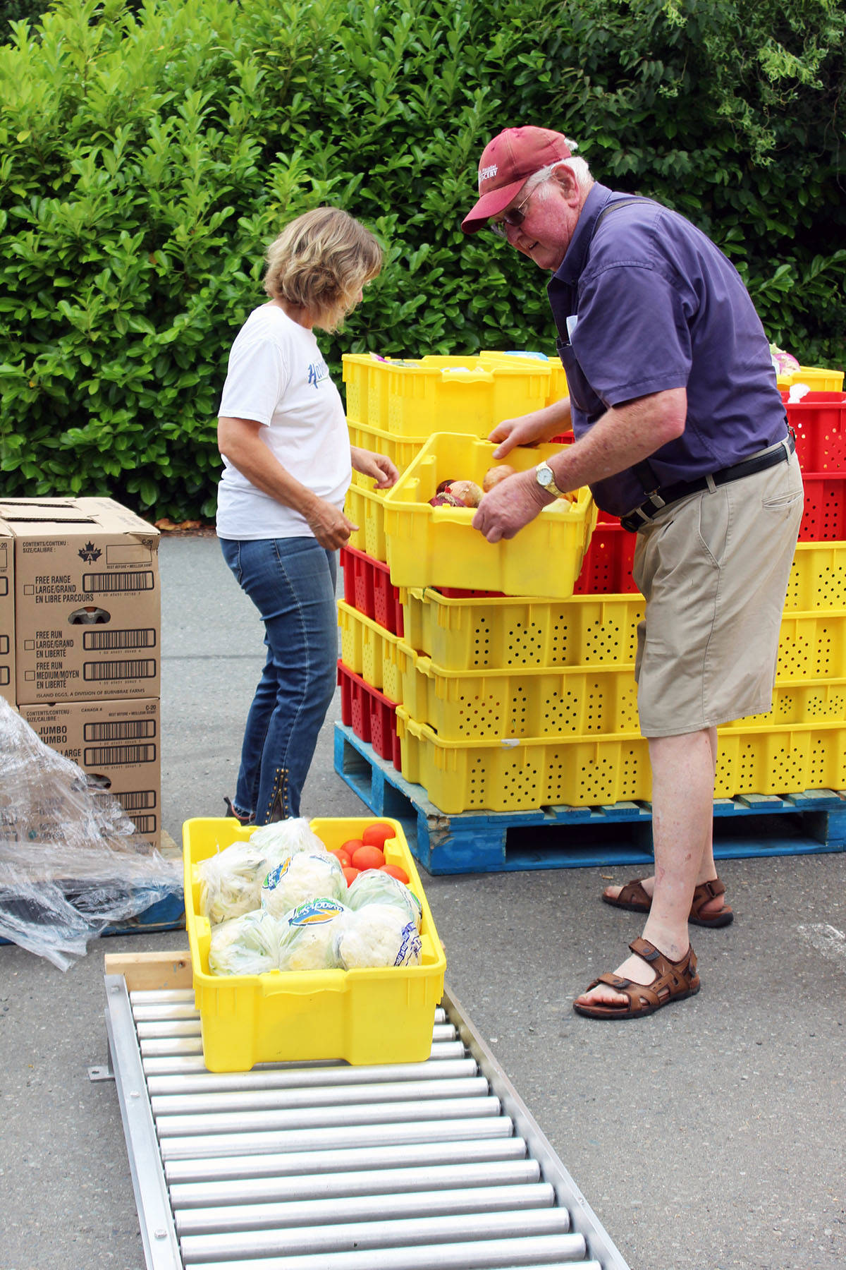 Jan Aikman and John Siebring sort through food outside the Chemainus United Church basement. (Photo by Don Bodger)