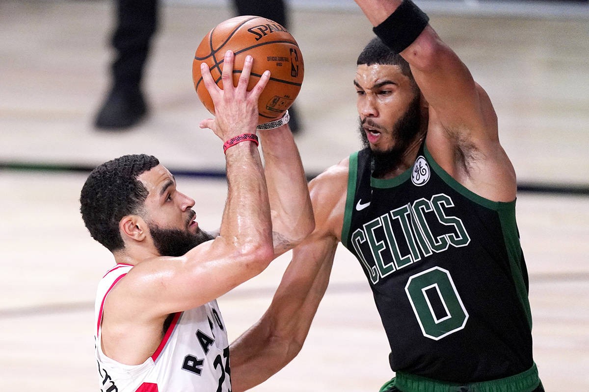 Toronto Raptors' Fred VanVleet, left, goes up for a shot against Boston Celtics' Jayson Tatum during the first half of an NBA conference semifinal playoff basketball game Friday, Sept. 11, 2020, in Lake Buena Vista, Fla. (AP Photo/Mark J. Terrill)