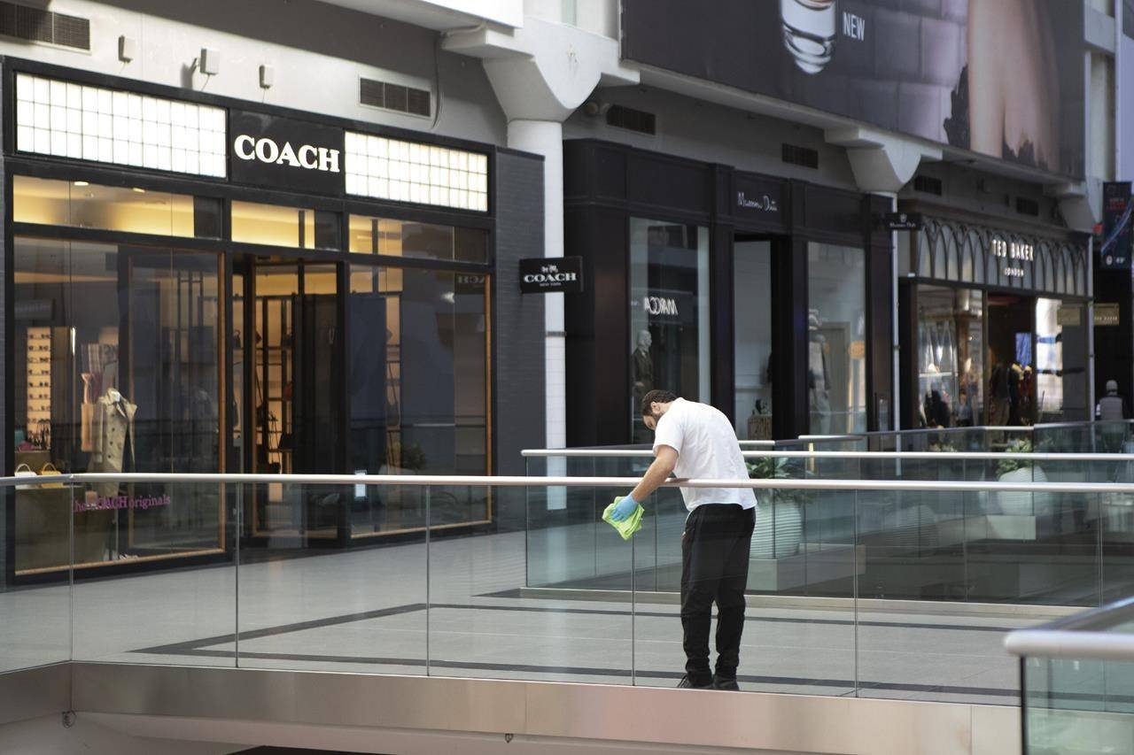 A cleaner wipes a glass panel at Toronto's Eaton Centre Shopping mall on Saturday, March 21, 2020. THE CANADIAN PRESS/Chris Young