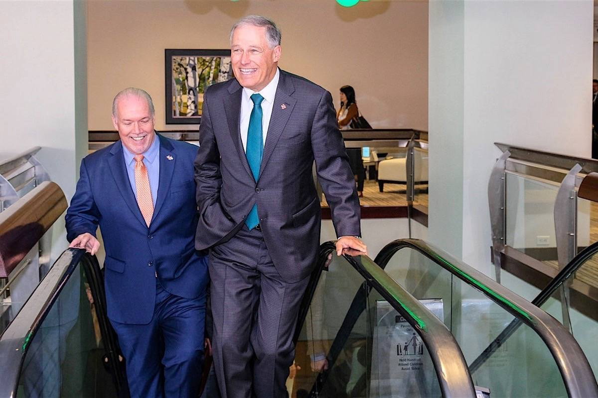 B.C. Premier John Horgan and Washington Gov. Jay Inslee arrive for annual Cascadia conference in Vancouver, Oct. 10, 2018. They have agreed to coordinate the permanent switch to daylight saving time. (B.C. government)