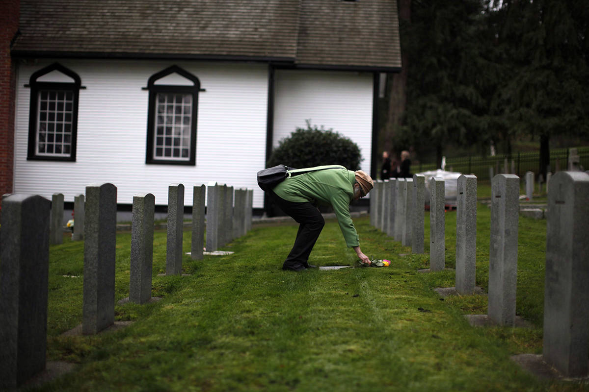 A woman lays flowers following Remembrance Day ceremonies at God's Acre Veteran's Cemetery in Victoria, B.C., on Sunday, November 11, 2018. THE CANADIAN PRESS/Chad Hipolito
