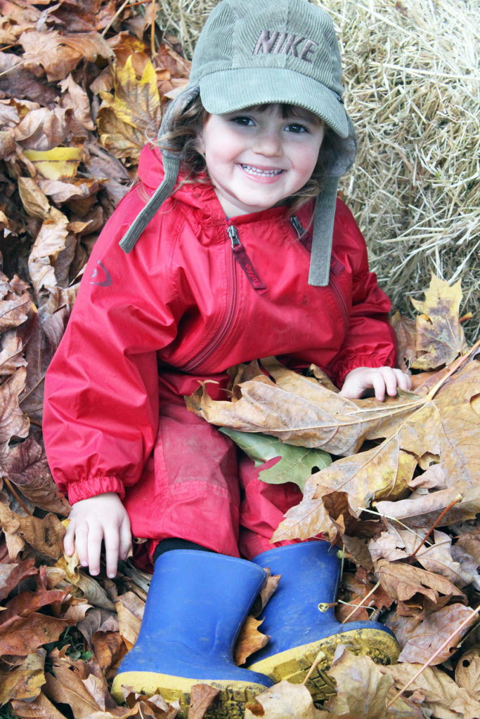 Charlie Burrow enjoys a frolic in leaves at Yellow Submarine Family Child Care. (Photo by JoHannah Knight)
