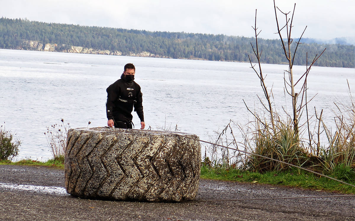 Size of the tires taken out of Chemainus Bay is put in perspective next to one of the Fleet Diving Unit members. (Photo by Kathleen Fenner)