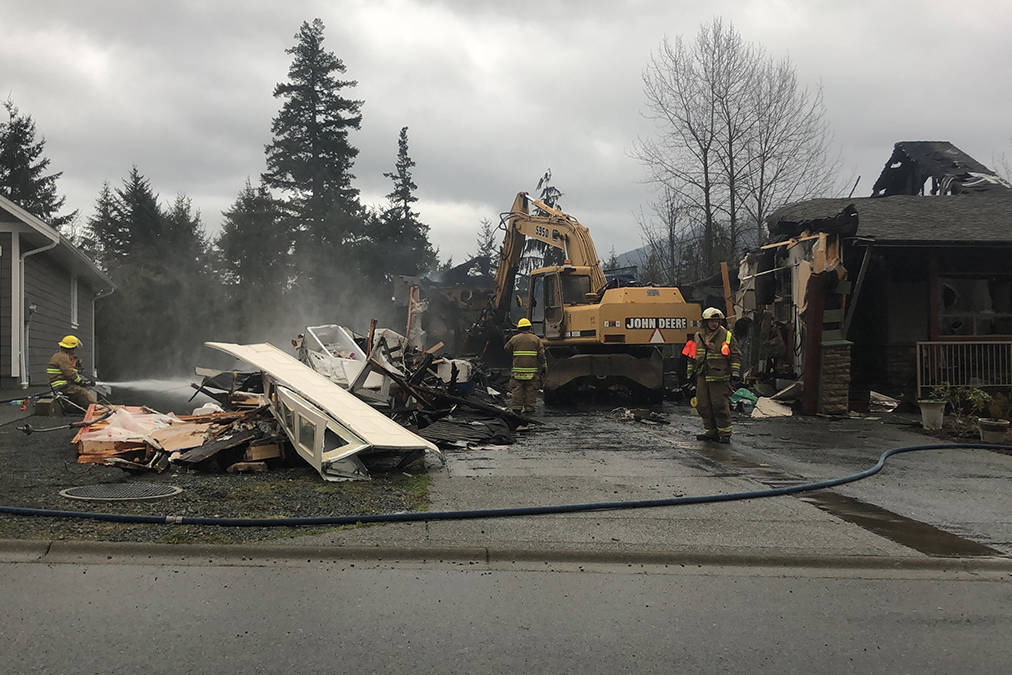 Equipment demolished what is left of a house on Mountain View Drive near Lake Cowichan after a house fire this morning, Nov. 27, 2020, as firefighters continued to pump water onto the smouldering remains. (Sarah Simpson/Gazette)