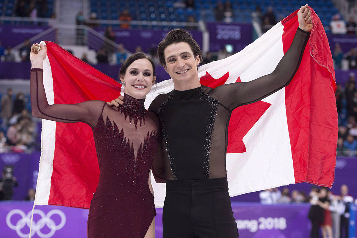 TUESDAY OLYMPIC REPEATS Ice dance gold medallists Canada's Tessa Virtue and Scott Moir hold up the Canadian flag during victory ceremonies at the Pyeongchang Winter Olympics Tuesday, February 20, 2018 in Gangneung, South Korea. THE CANADIAN PRESS/Paul Chiasson