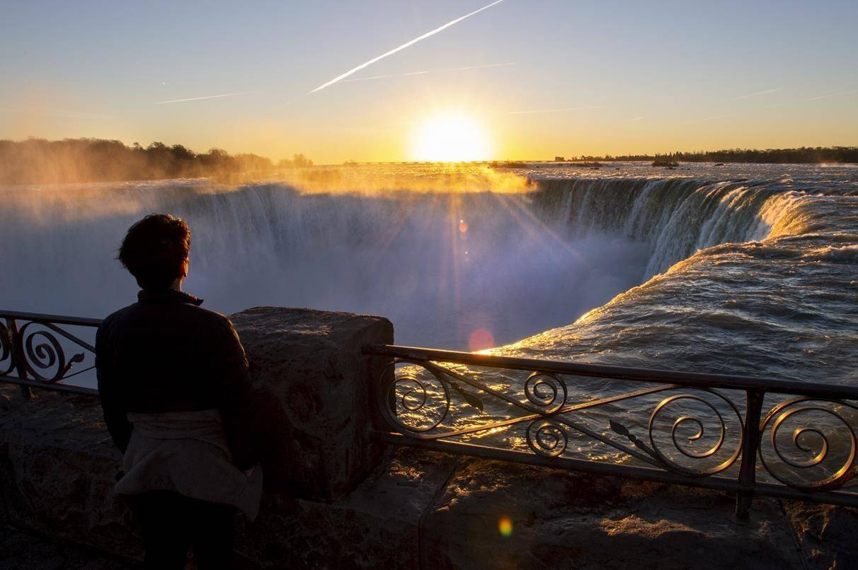 A man watches the sun rise over Niagara Falls in Niagara Falls, Ont. on Wednesday Nov. 4, 2020. Ottawa is rolling out a wave of new funding for pandemic-battered industries including tourism, the arts and regional aviation, with smaller companies top of mind — and large airlines notably absent. THE CANADIAN PRESS/Frank Gunn