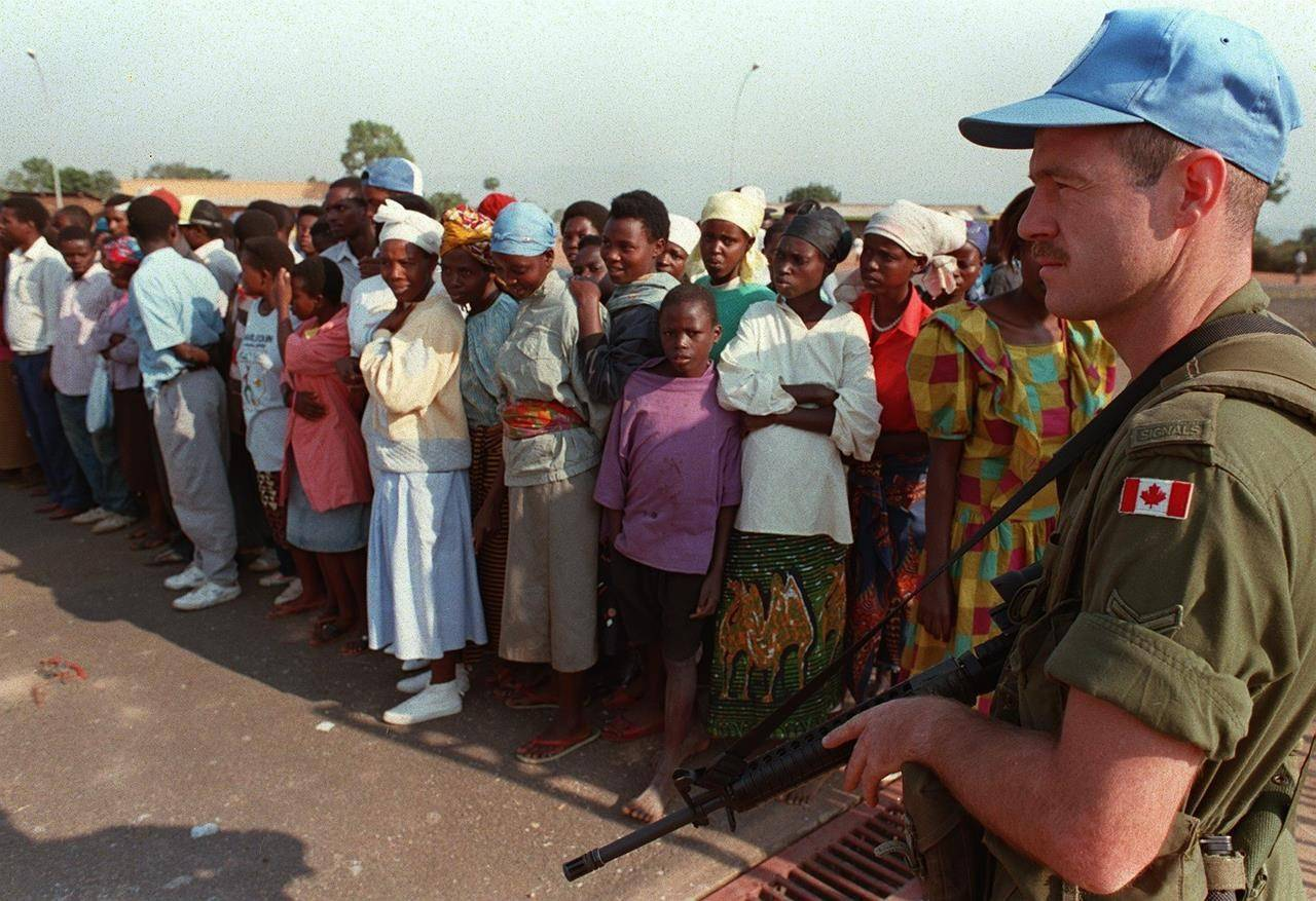 A Canadian peacekeeper watches a group of Rwandan refugees in Kigali, Rwanda, in this August 1994 photo. THE CANADIAN PRESS/Ryan Remiorz