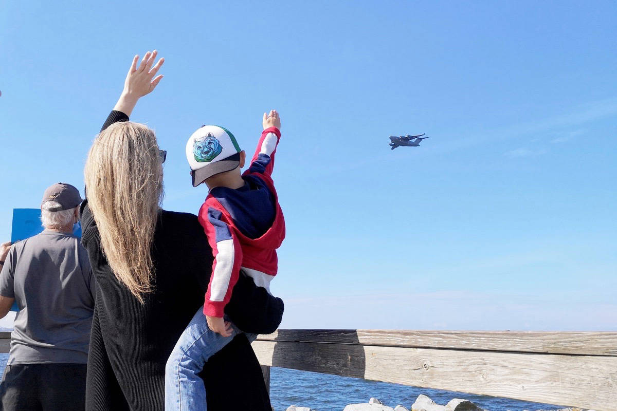 Four-year-old Ethan Fritz waves at his dad with his mom Alyssa, Aug. 7, from the end of White Rock Pier. Pilot TK Minzak – who flies reserve for the U.S. Air Force, organized the fly-by after months of not being able to see Ethan due to border restrictions during the pandemic. The approach of a U.S. military aircraft caught more than a few White Rock residents and visitors off-guard. (Tracy Holmes/Peace Arch News)