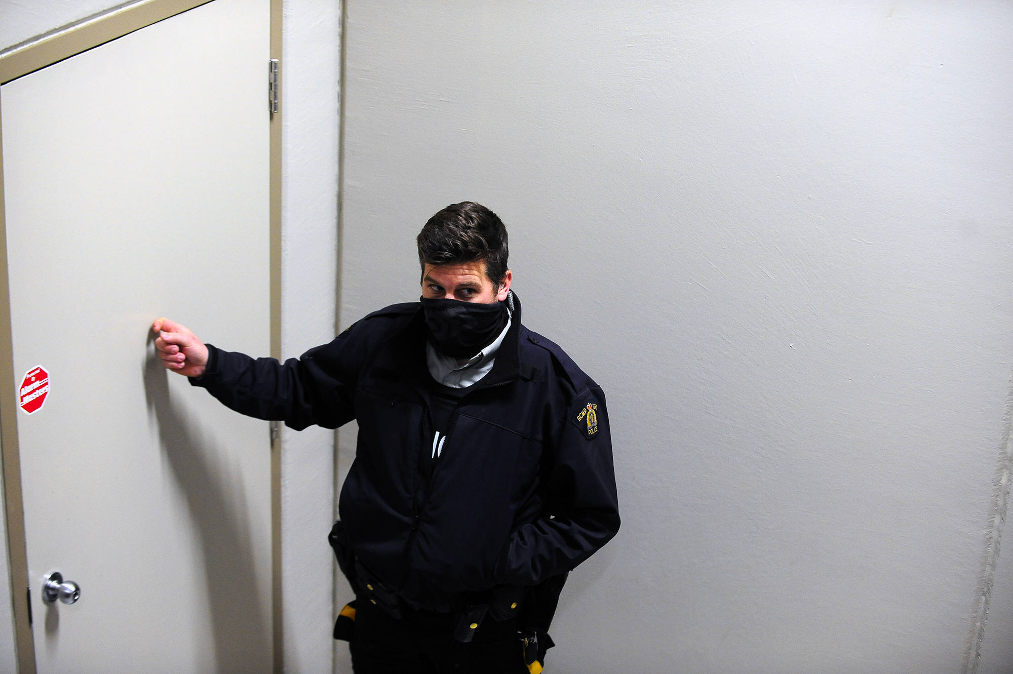 An RCMP officer knocks on the door where parishioners of Kelowna Harvest Fellowship are gathering on Sunday, Jan. 10. (Michael Rodriguez - Capital News)