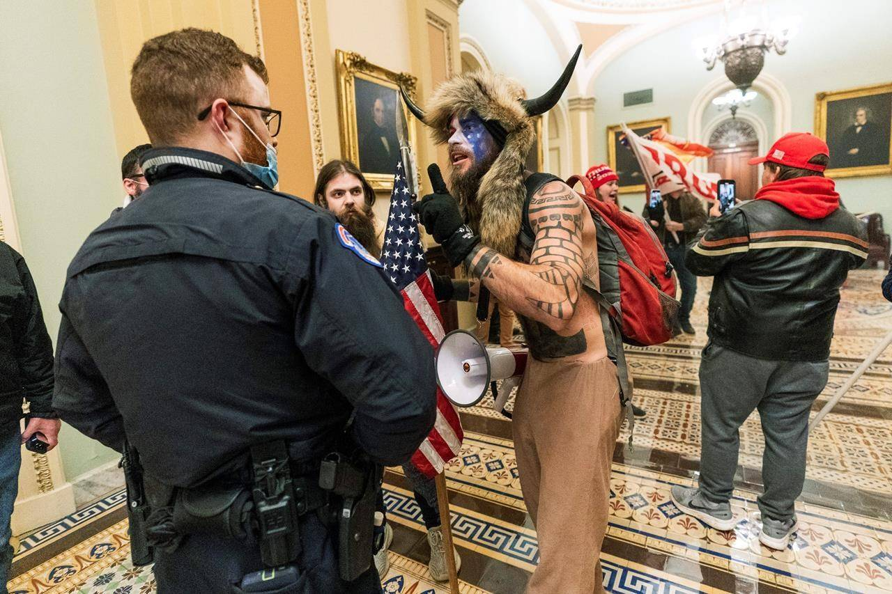 FILE - In this Jan. 6, 2021, file photo supporters of President Donald Trump are confronted by U.S. Capitol Police officers outside the Senate Chamber inside the Capitol in Washington. An Arizona man seen in photos and video of the mob wearing a fur hat with horns was also charged Saturday in Wednesday's chaos. Jacob Anthony Chansley, who also goes by the name Jake Angeli, was taken into custody Saturday, Jan. 9. (AP Photo/Manuel Balce Ceneta, File)