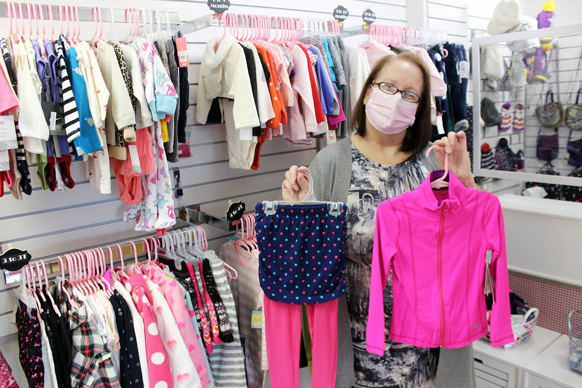 Carol Hodgins with some of the abundant clothing she carries in Little Angels Children's Boutique. (Photo by Don Bodger)
