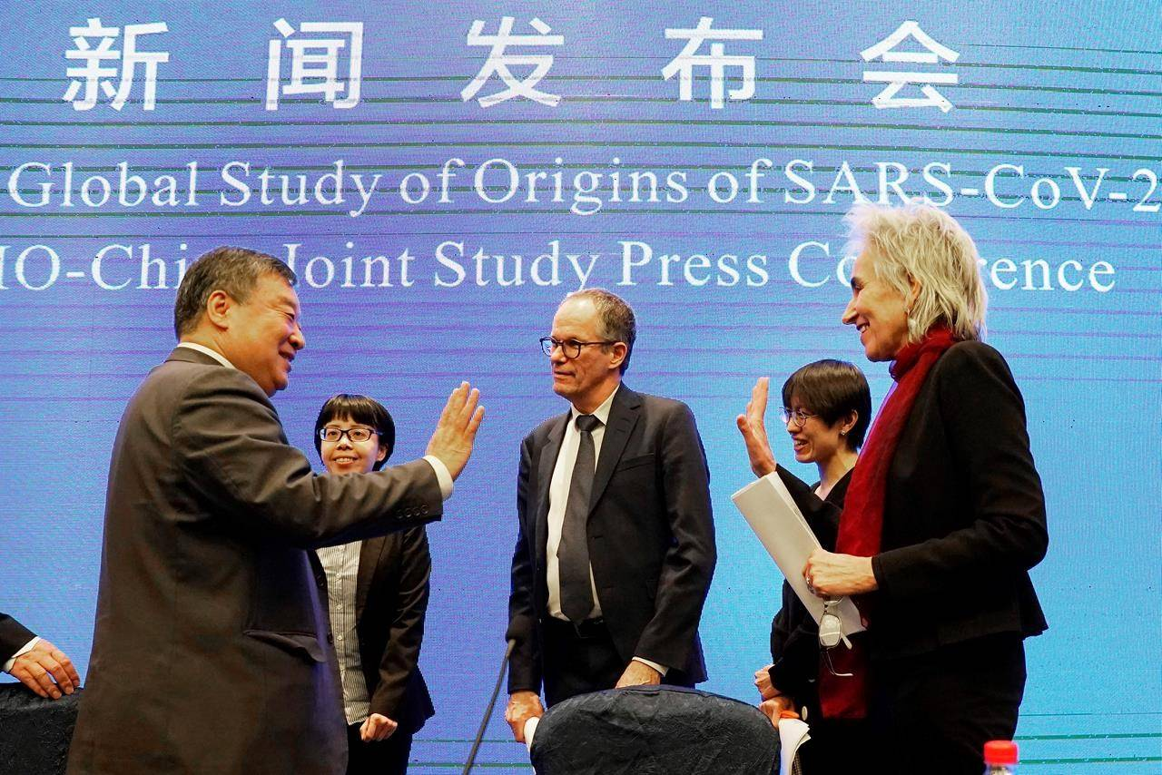 Marion Koopmans, right, and Peter Ben Embarek, center, of the World Health Organization team say farewell to their Chinese counterpart Liang Wannian, left, after a WHO-China Joint Study Press Conference held at the end of the WHO mission in Wuhan, China, Tuesday, Feb. 9, 2021. (AP Photo/Ng Han Guan)