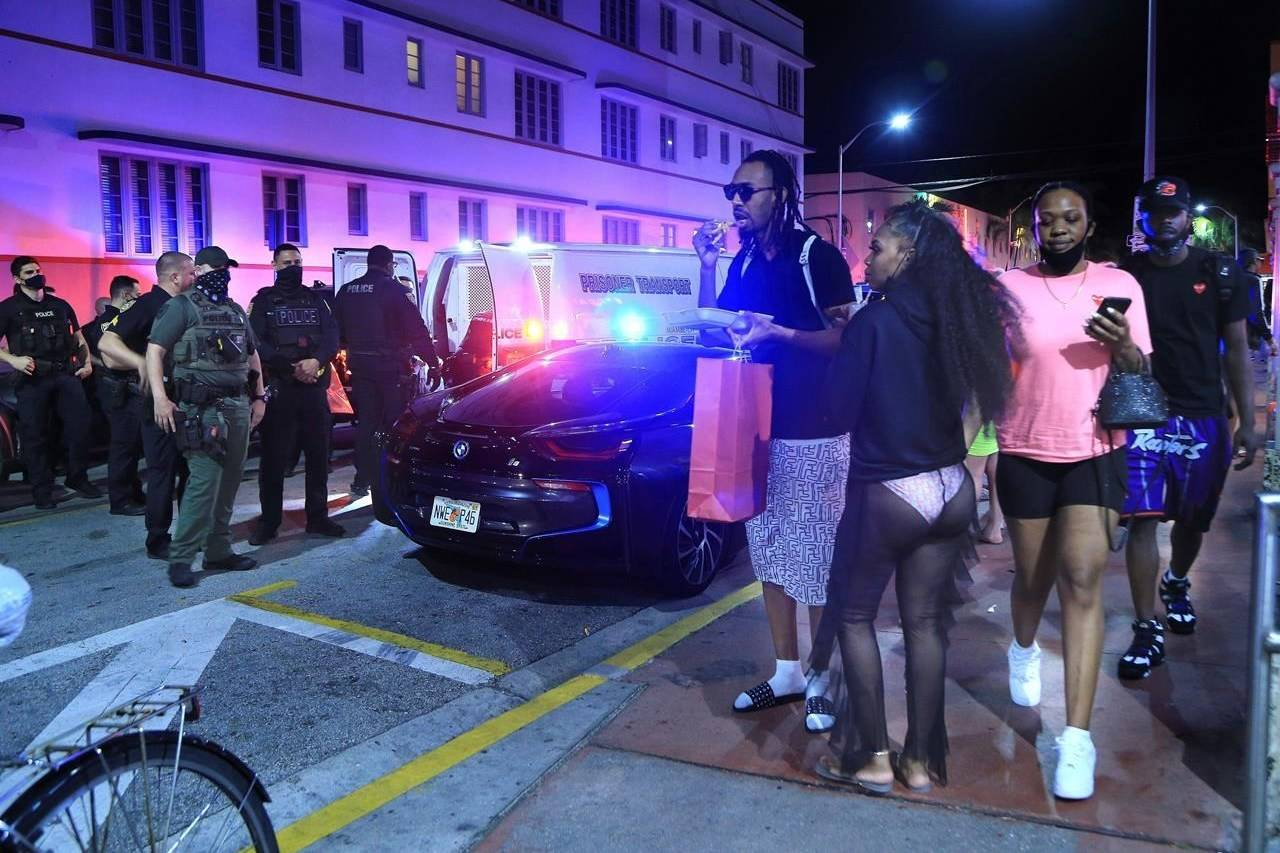 People watch as City of Miami Beach Police officers arrest several males on Ocean Drive and 10th Street as spring break has officially begun, Saturday, Feb. 20, 2021 in Miami Beach, Fla. Miami Beach officials are imposing an emergency 8 p.m.-6 a.m. curfew effective immediately, saying large, out-of-control spring break crowds crammed the beaches, trashed some restaurant properties and brawled in the streets. Tourists and hotel guests are being told to stay indoors during the curfew hours. (Pedro Portal/Miami Herald via AP)