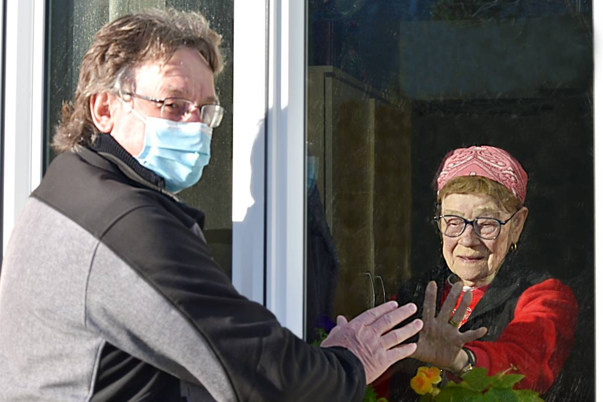Rose Sawka, 91, reaches out to her son Terry Sawka, on a daily visit through the window at Acropolis Manor in Prince Rupert, Jan. 30, 2021. (K-J Millar/The Northern View)
