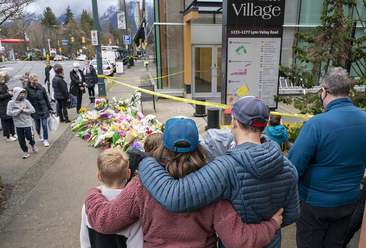 A family embraces at a makeshift memorial outside of the Lynn Valley Library in Lynn Valley in North Vancouver, B.C., Sunday, March 28, 2021. A 28-year-old man was charged Sunday with second-degree murder in a stabbing rampage that left a young woman dead and injured six others in and around a library in North Vancouver, B.C., a day earlier. THE CANADIAN PRESS/Jonathan Hayward