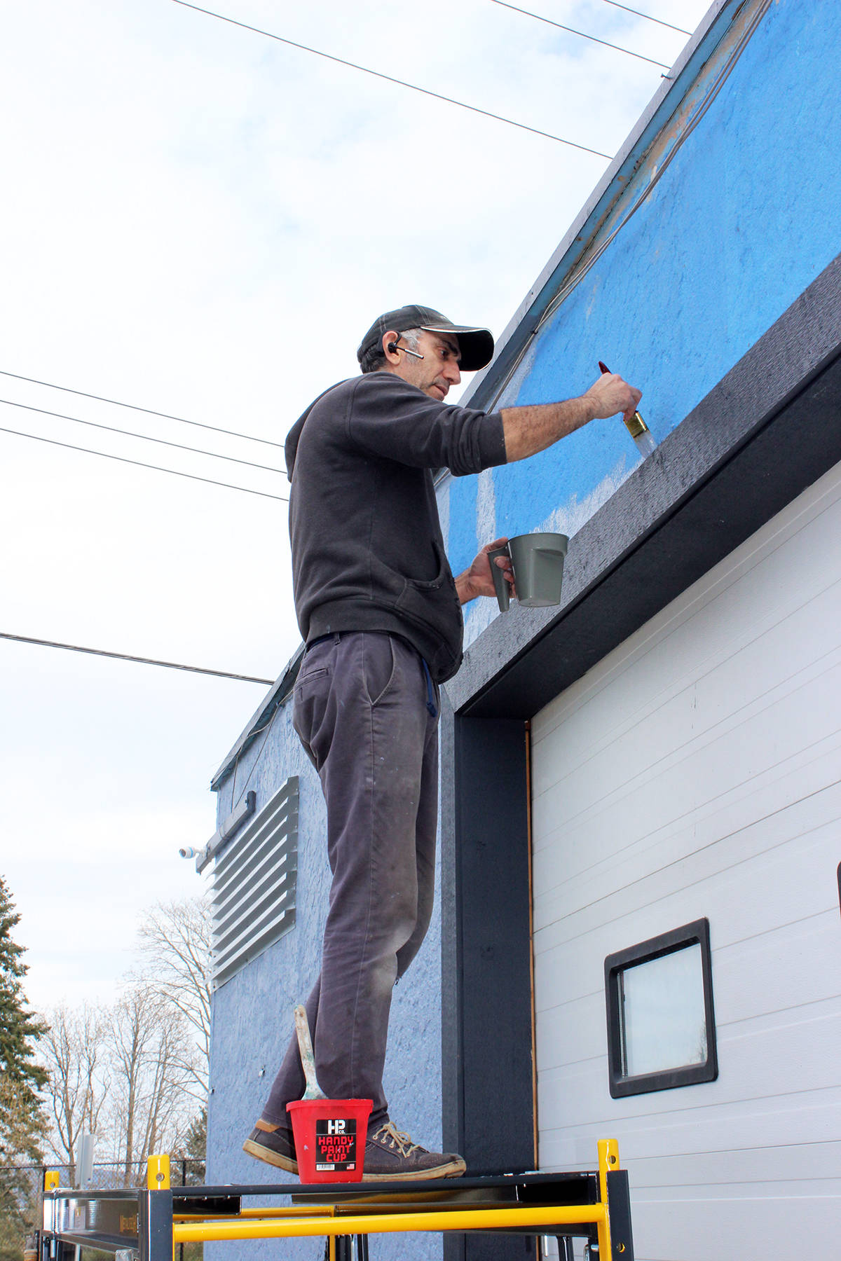 The much-maligned blue building on Chemainus Road is getting a paint job. Building owner Blake Sam is working on converting it to an Oxford grey colour with Benjamin Moore point. (Photo by Don Bodger)