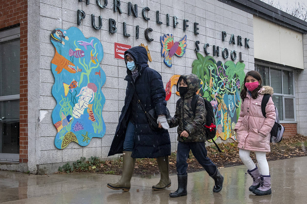 FILE – A family walk past the sign at Thorncliffe Park Public School in Toronto on Friday December 4, 2020. THE CANADIAN PRESS/Frank Gunn