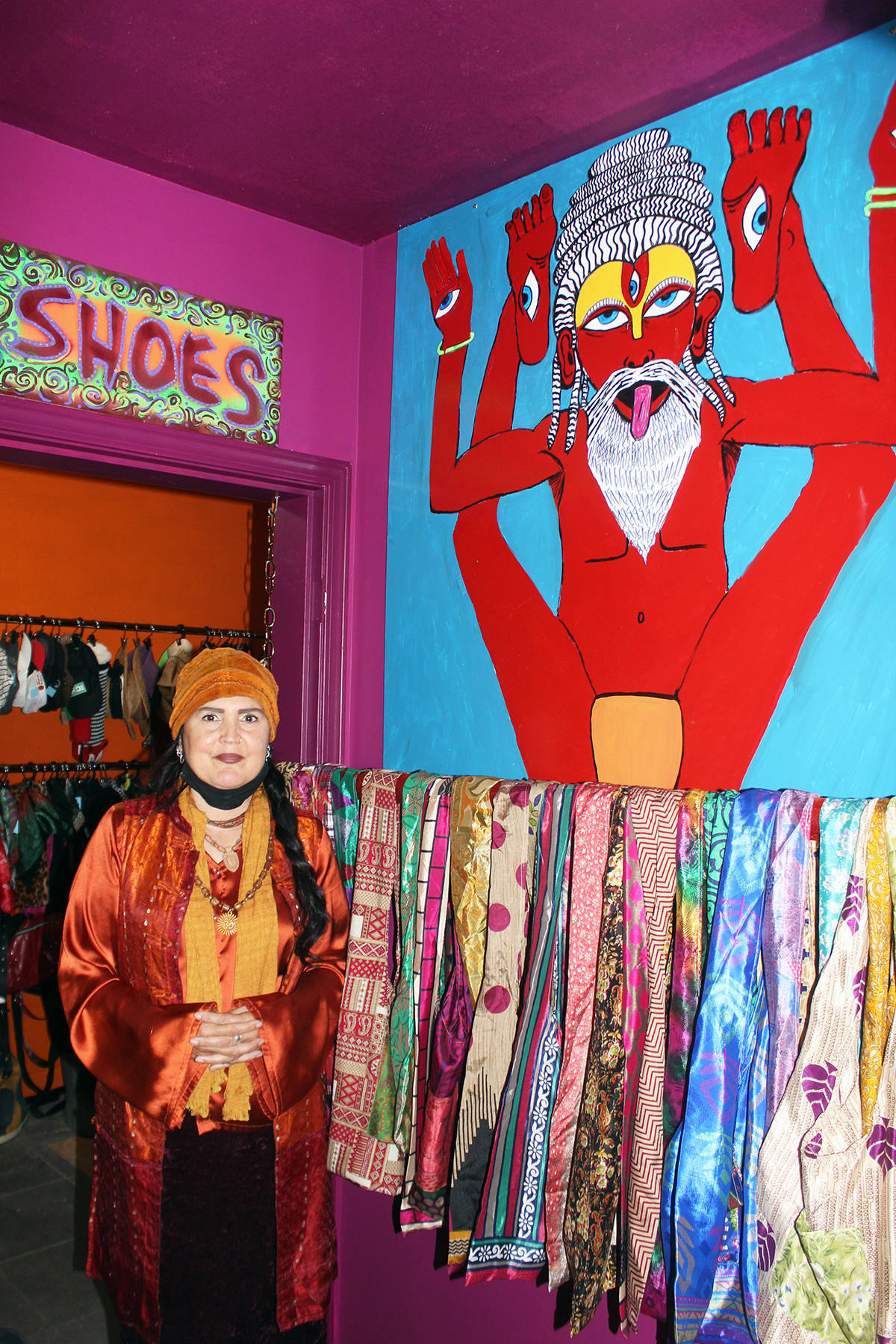 Colourful art on the walls is matched by colourful scarves in Morgan McLeod's Govinda's Thrift Store. (Photo by Don Bodger)