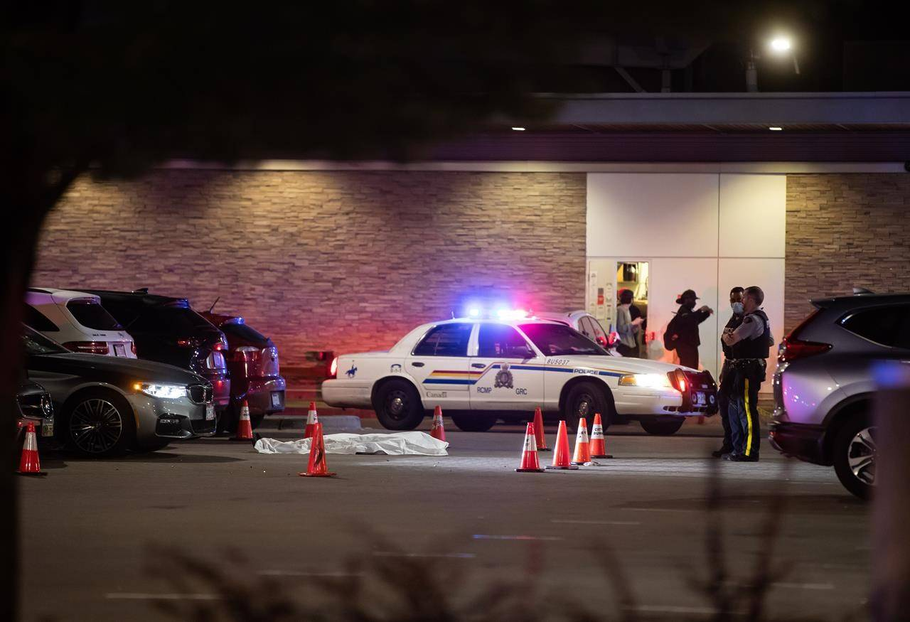 RCMP officers stand near a body covered with a tarp in the parking lot of a shopping complex after Brothers Keepers member Jaskeert Kalkat, 23, was killed during a shooting in Burnaby on May 13, 2021. THE CANADIAN PRESS/Darryl Dyck