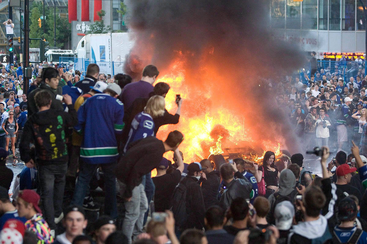 People watch a car burn during a riot following game 7 of the NHL Stanley Cup final in downtown Vancouver, B.C., in this June 15, 2011 photo. THE CANADIAN PRESS/Geoff Howe