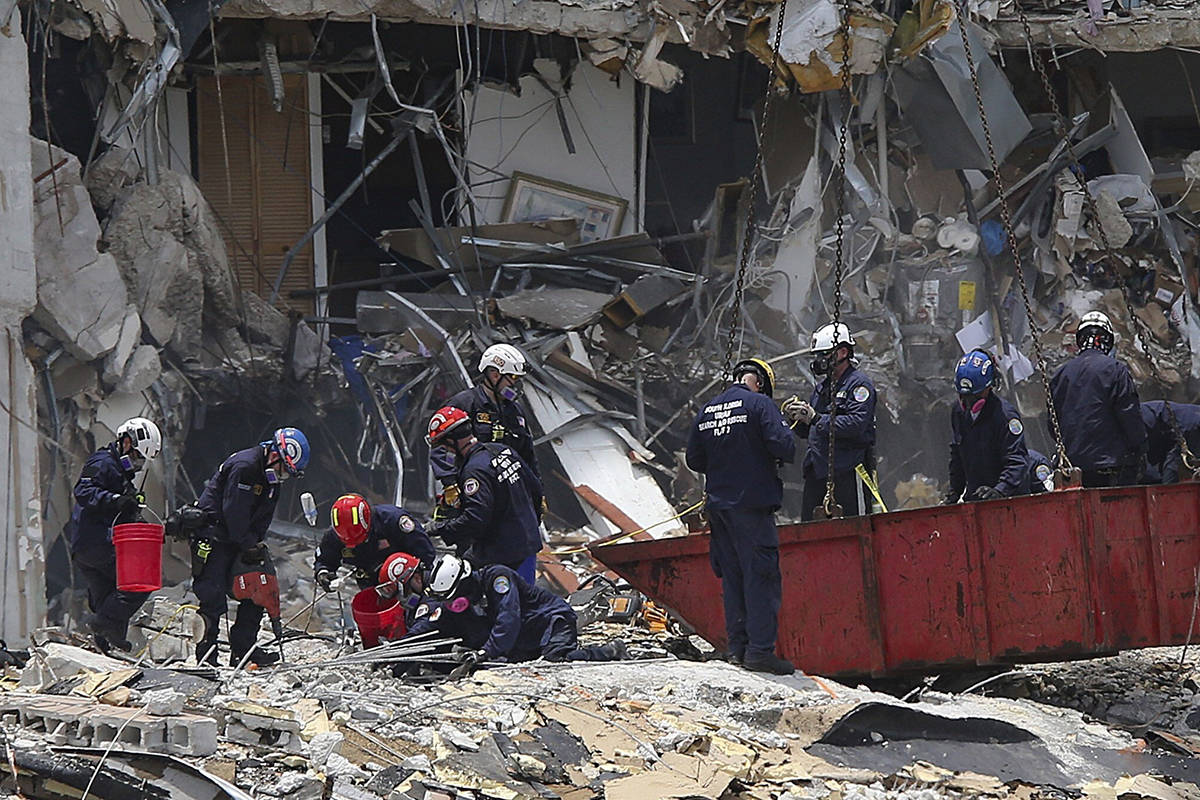 South Florida Urban Search and Rescue team look for survivors at the 12-story oceanfront condo, Champlain Towers South on Saturday, June 26, 2021 that partially collapsed early Thursday morning in the Surfside area of Miami. (Al Diaz/Miami Herald via AP)