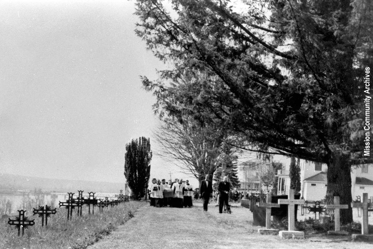 A 1958 photo of Father Falhman's funeral procession at the Oblates of Mary Immaculate Cemetery at St. Mary's Residential School. The graves on the hill left-hand side of the photo are now covered by row of blackberry bushes. Mission Community Archives photo.