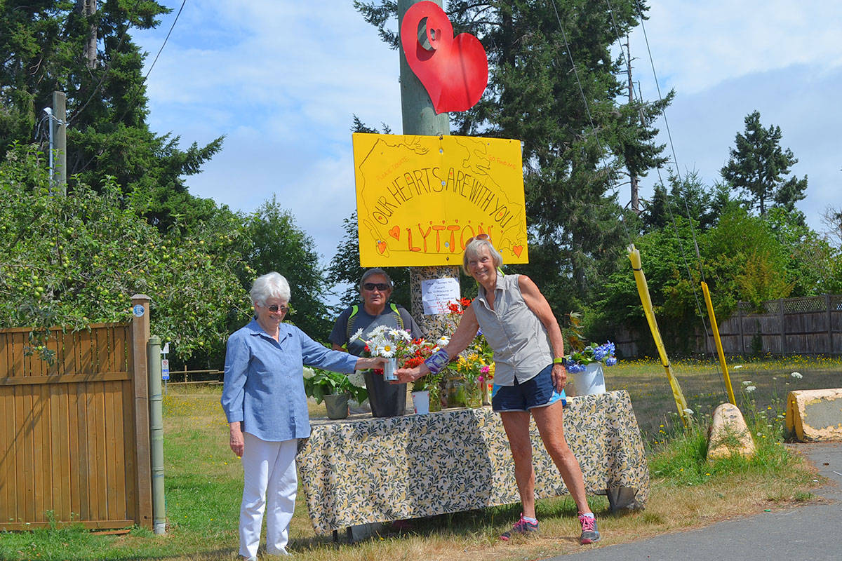 Sheri Plummer, right, and Sally Soanes hold a freshly donated bouquet of daises for the 'Our Hearts Are With You, Lytton' awareness stand on the corner of Wright Road and Sunray Road in Parksville. (Mandy Moraes)