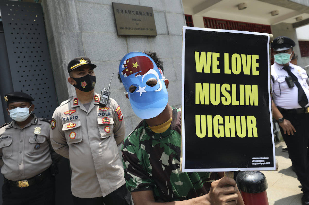 A Muslim student wearing a mask with the colors of the pro-independence East Turkistan flag, holds a poster during a rally outside the Chinese Embassy in Jakarta, Indonesia, Thursday, March 25, 2021. About a dozen of students staged the rally calling to an end to alleged oppression against Muslim Uyghur ethnic minority in China's region of Xinjiang. (AP Photo/Dita Alangkara)